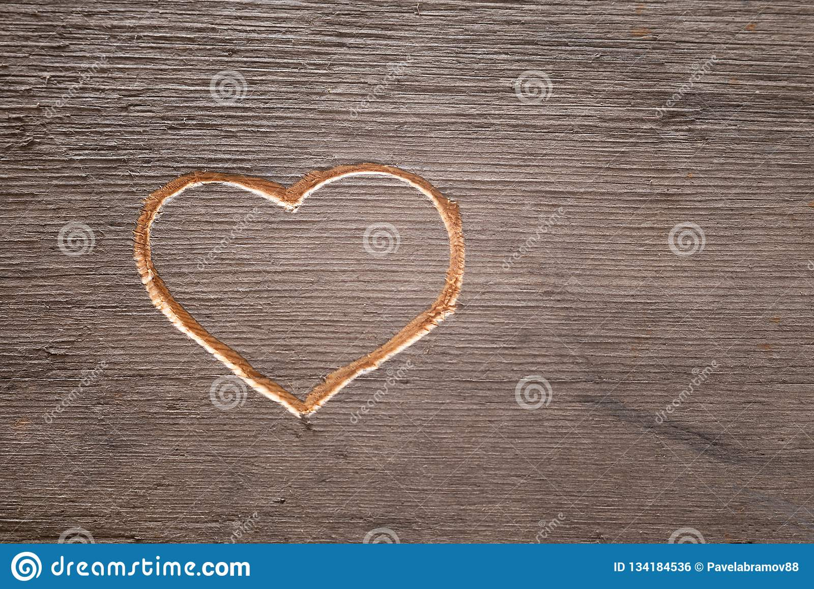 Heart carved on the wooden plank