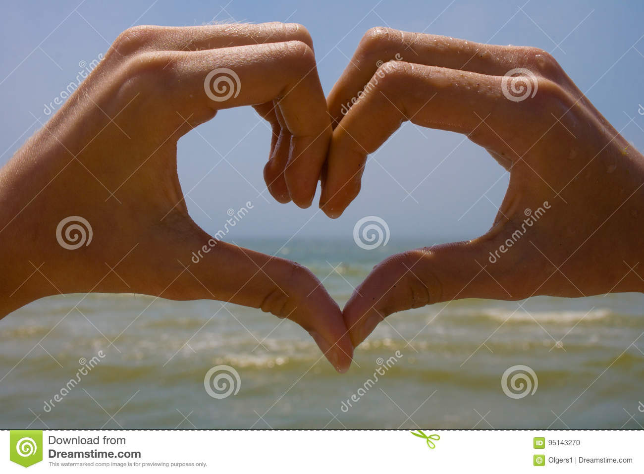 Heart from hands on the background of the sea