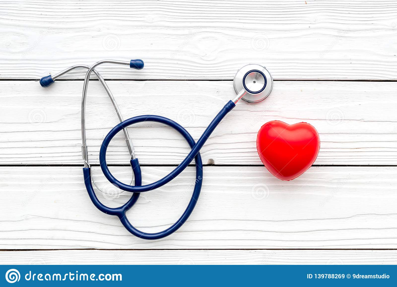Heart health, health care concept. Stethoscope near rubber heart on white wooden background top view space for text