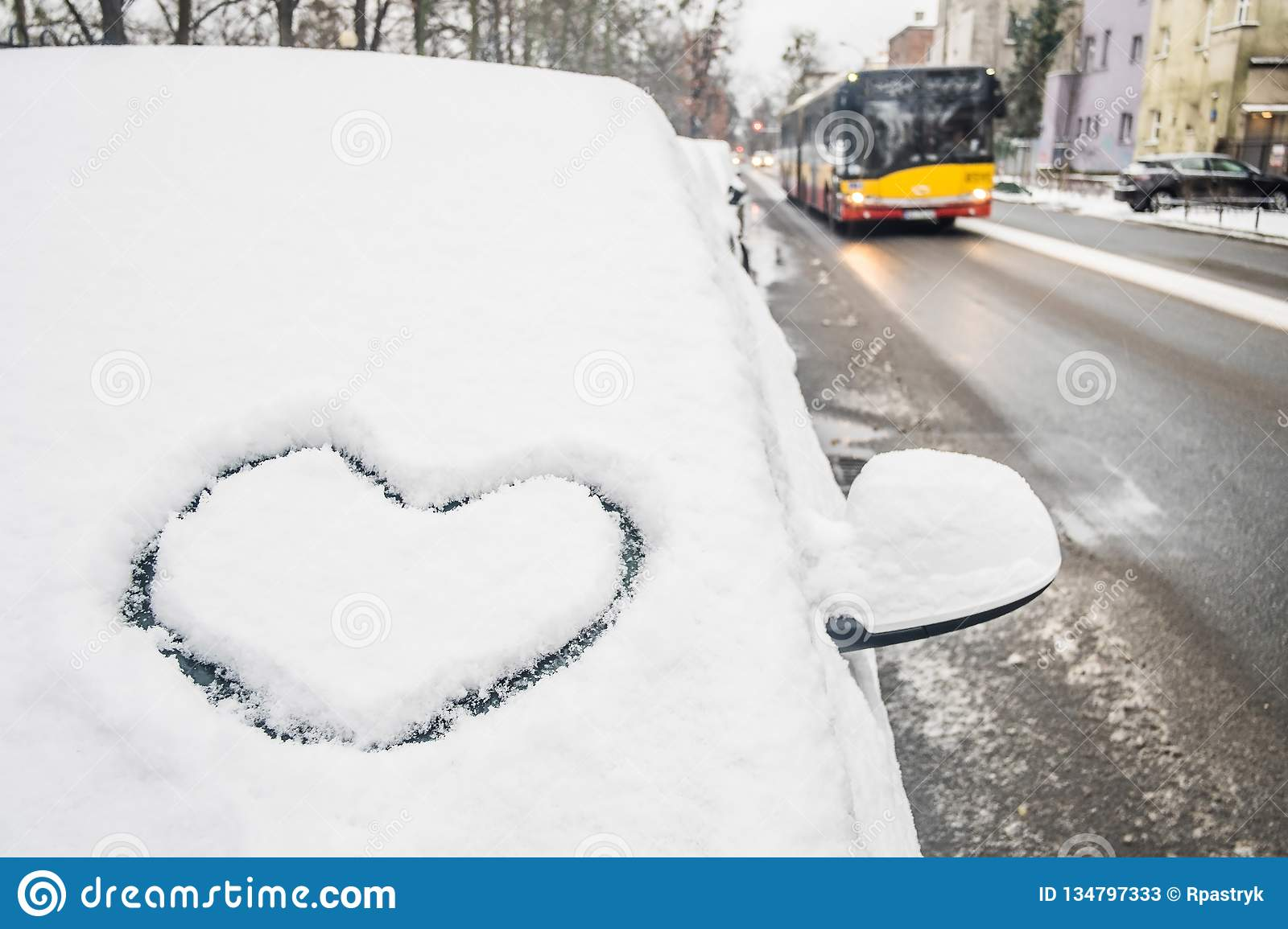 Heart icon drawing in snow on car front window, bus in the background