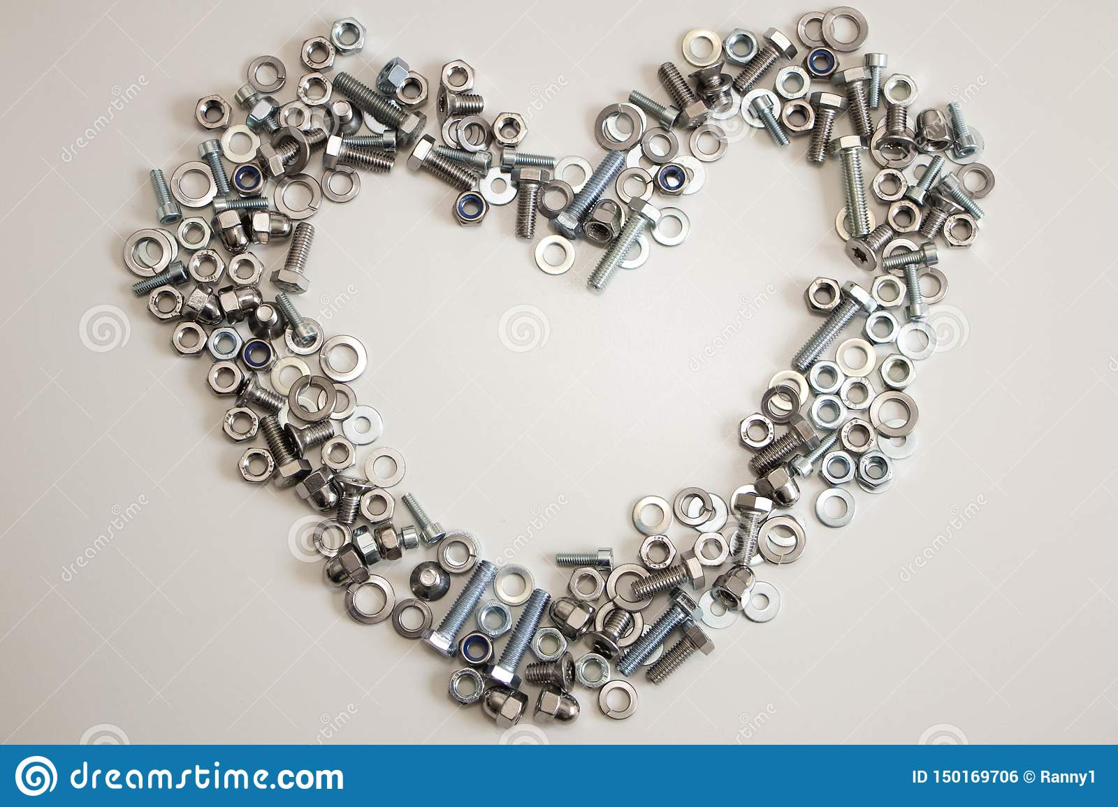A heart lined with a variety of nuts, bolts, screws and washers with empty space inside on a light gray background