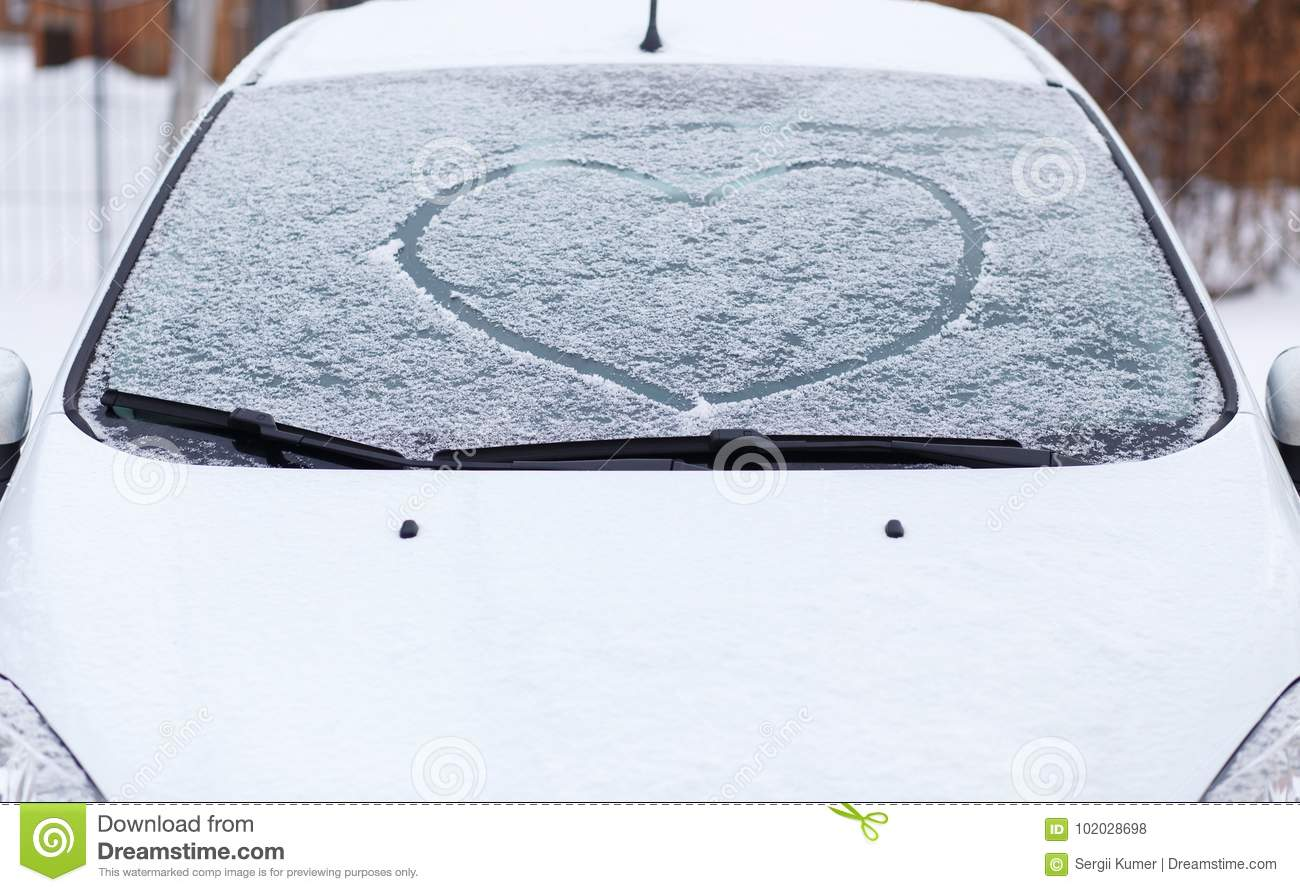Heart love symbol on windscreen of car in snow