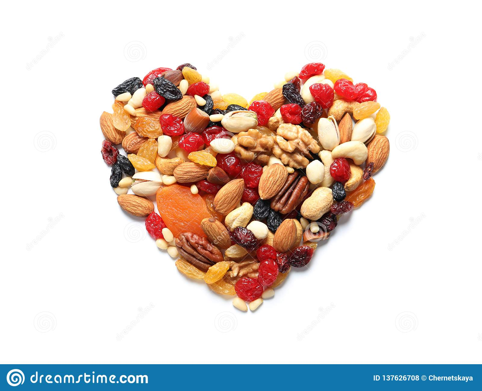 Heart made of dried fruits and nuts on white background
