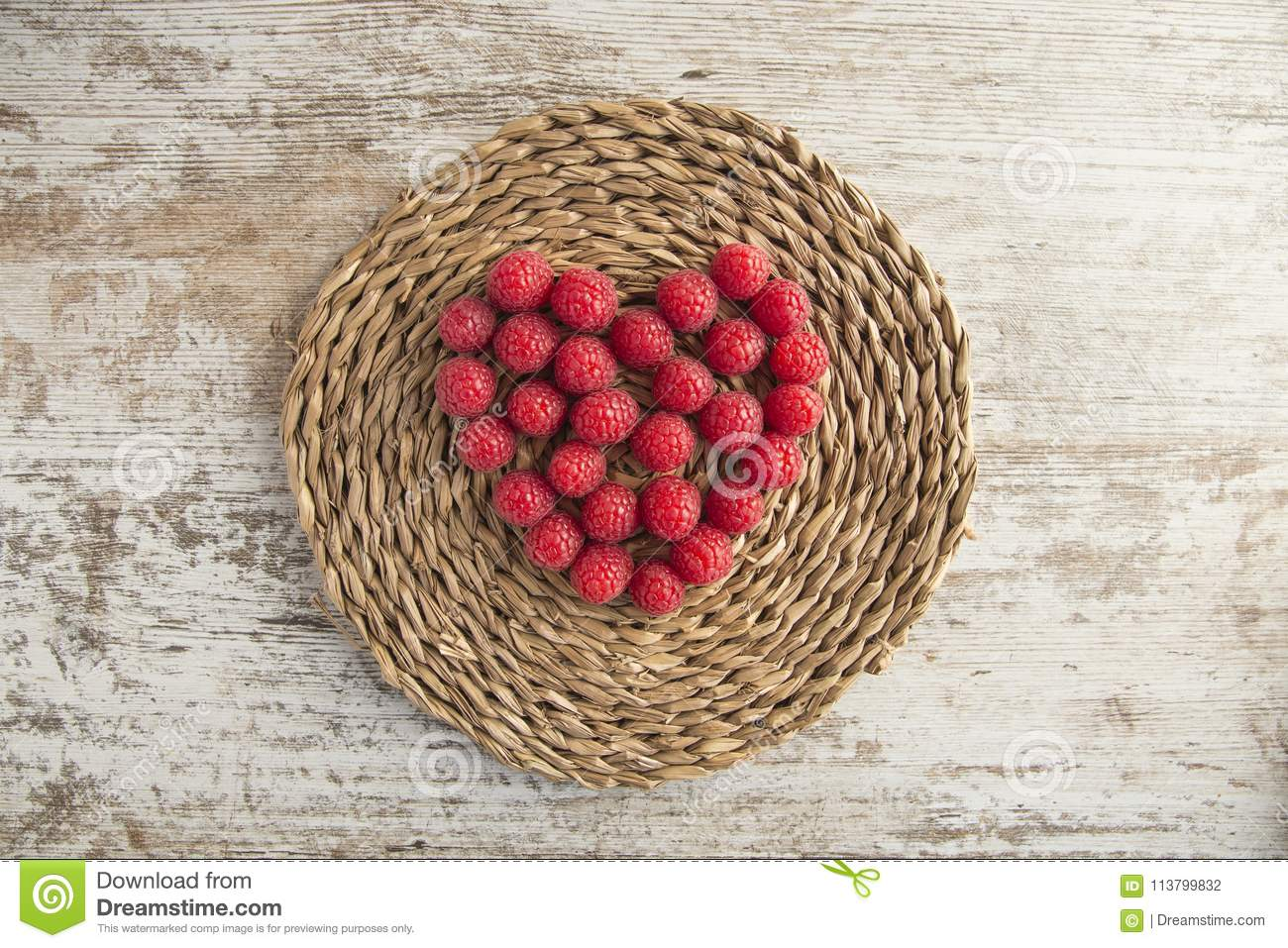 Heart made of raspberries on rustic background
