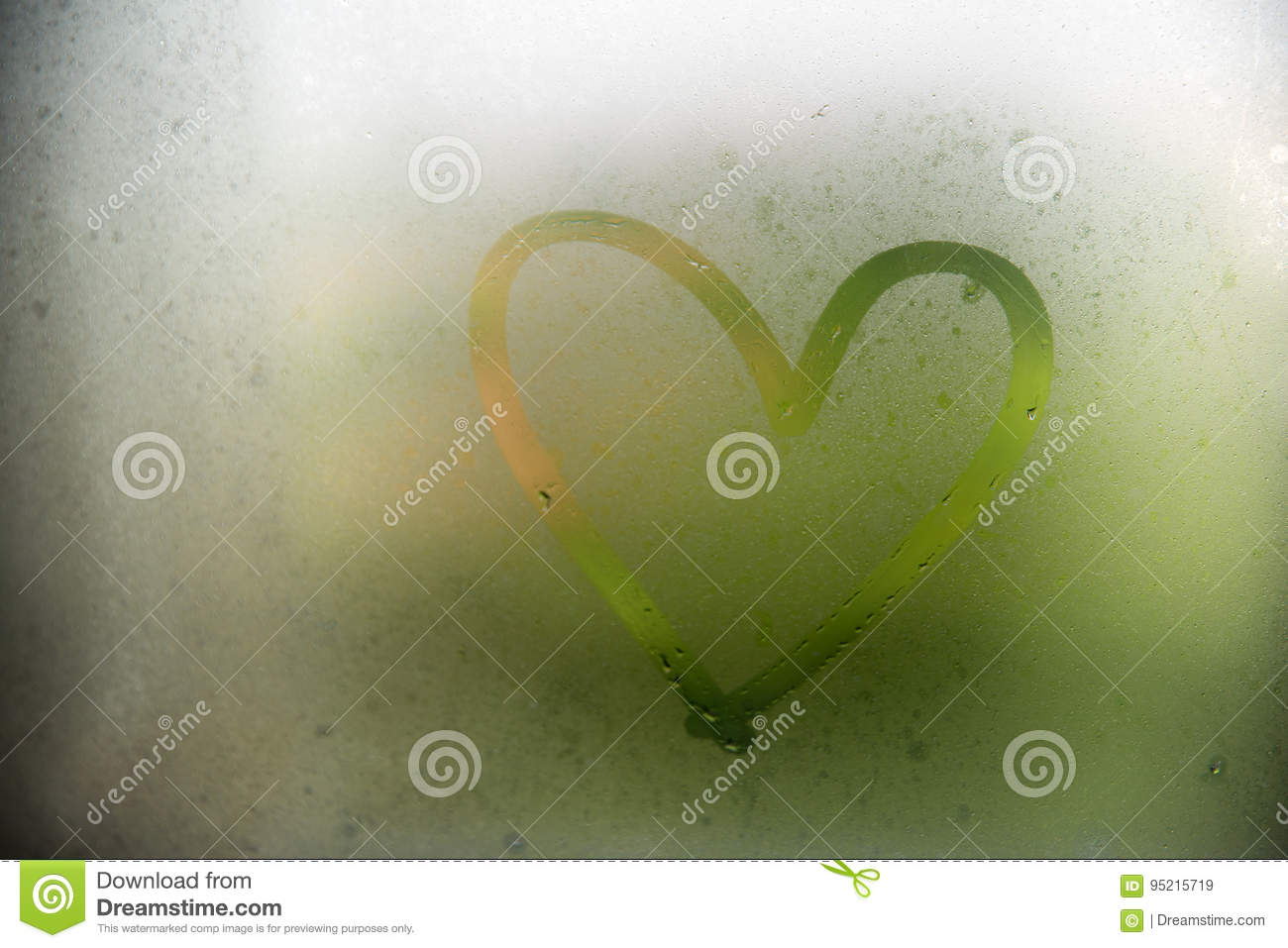 A heart painted on a misted window.Heart on misted glass. Heart on a window background