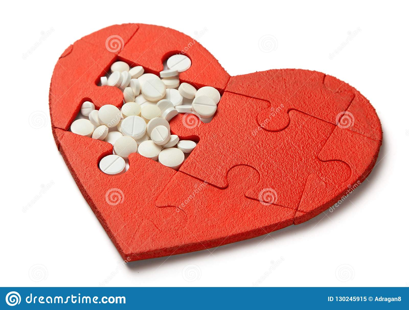 Heart puzzle red and white pills isolated on white background. Concept treatment of heart disease pills