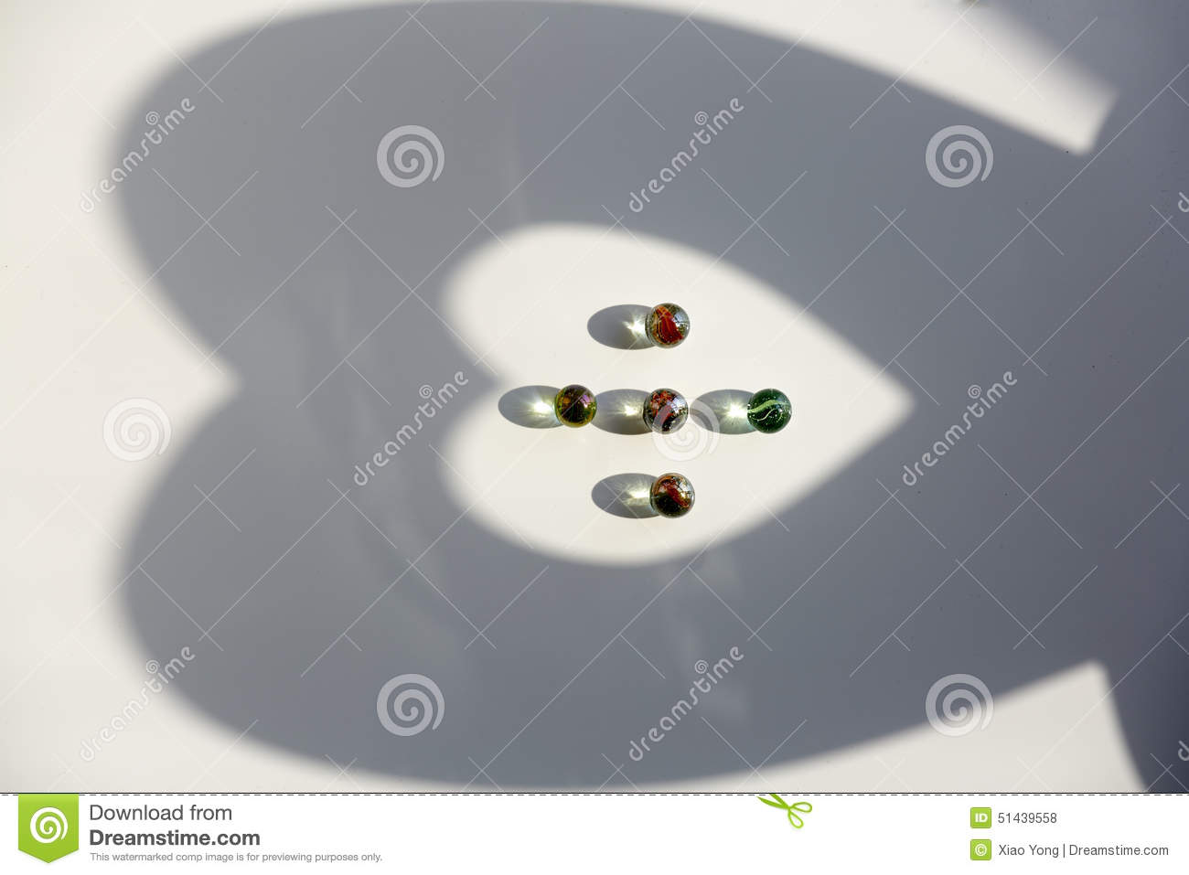 Heart shape, shining glass marbles and shadow