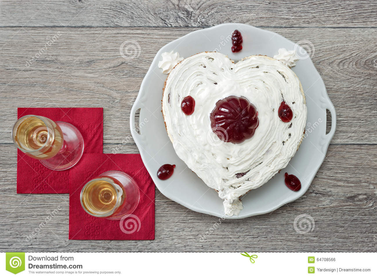 Heart shaped cake with red marmelade and two glasses of champagne served on napkins against wooden background for romantic date