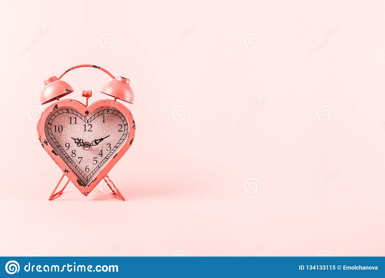 Heart shaped clock on pink background. Valentines day and love infitity and duration concept . Living coral theme - color of the