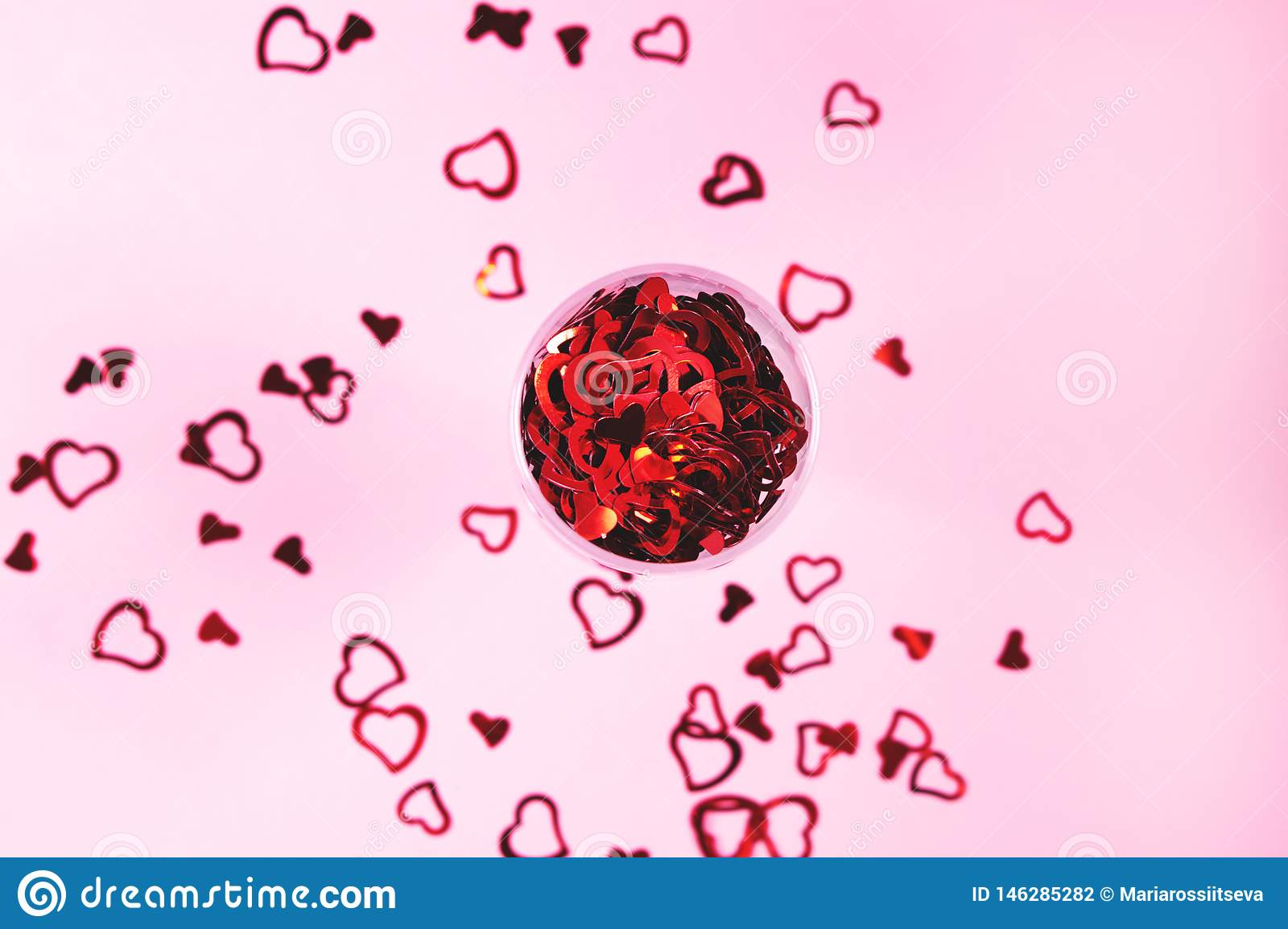 Heart-shaped confetti on pink background