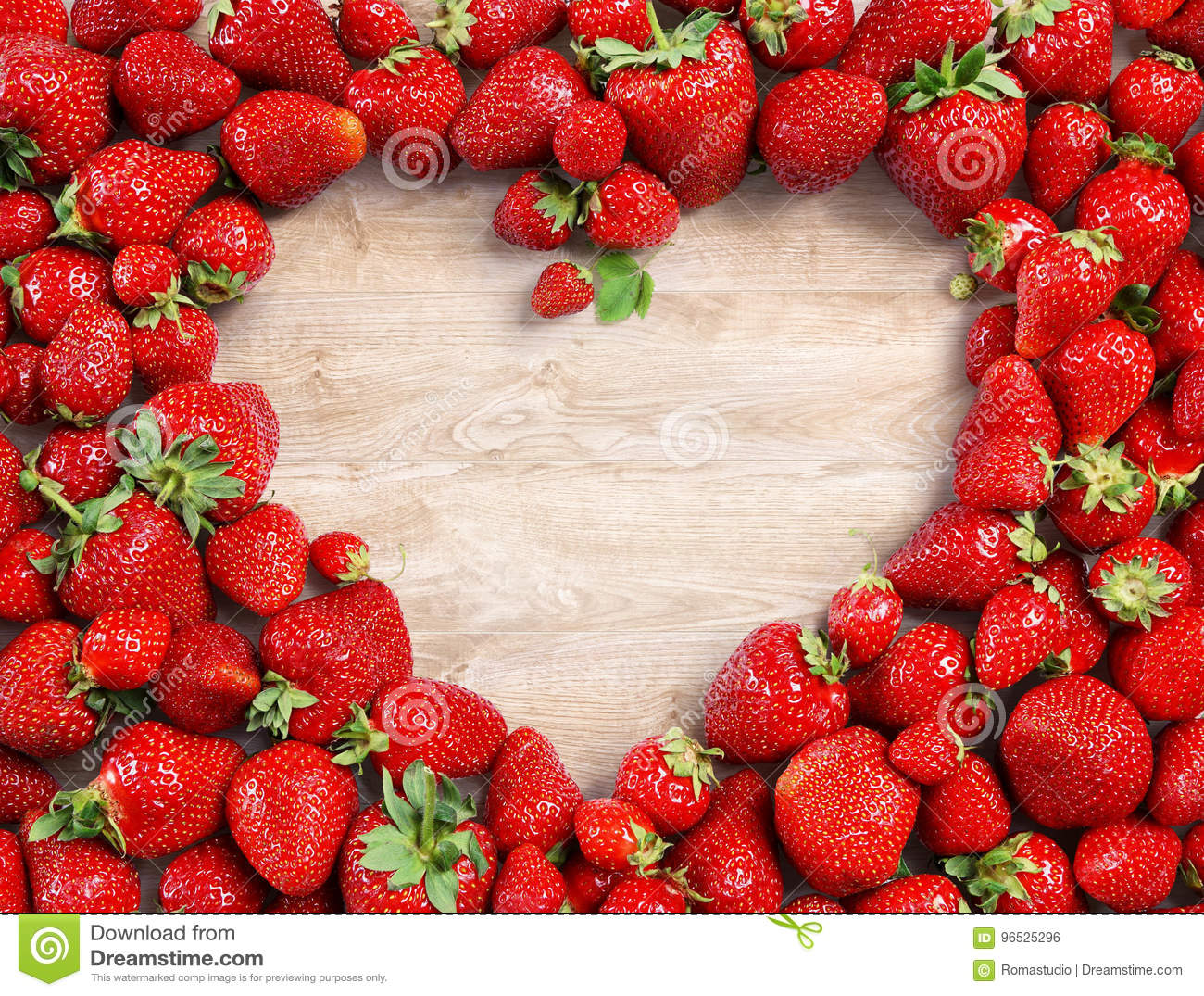 Heart shaped made of strawberry on wooden background.