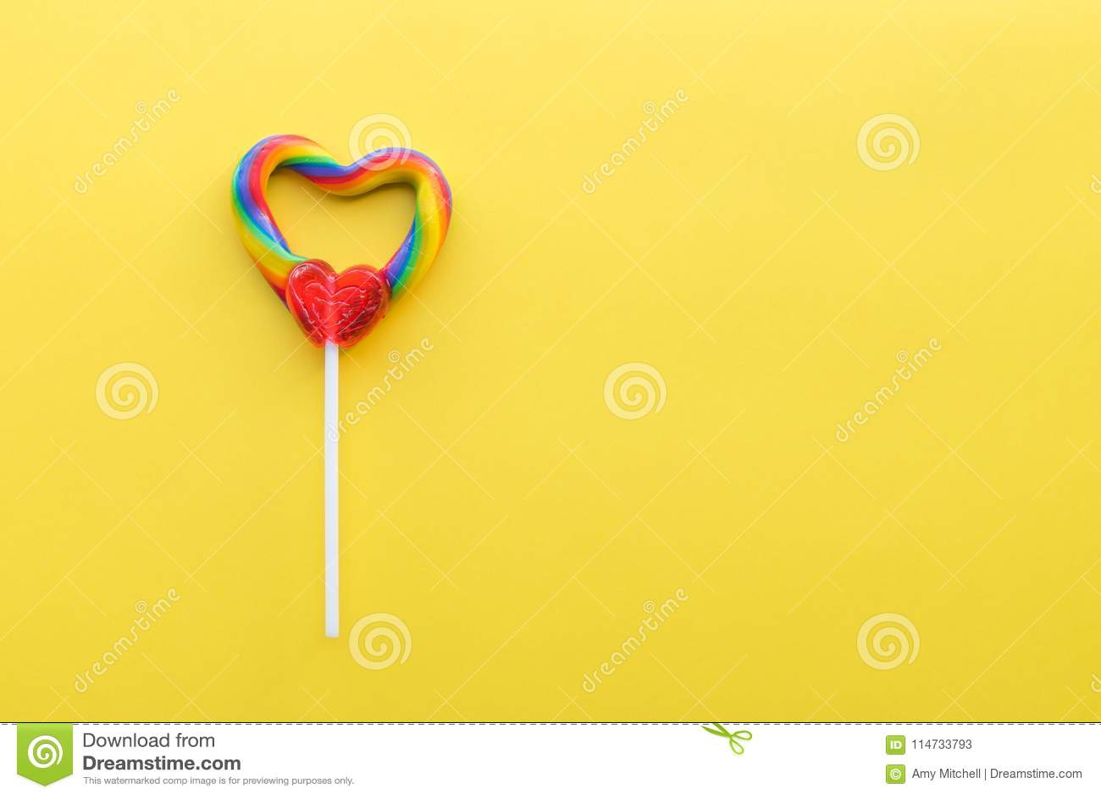 Heart shaped rainbow swirl lollipop on bright yellow solid background