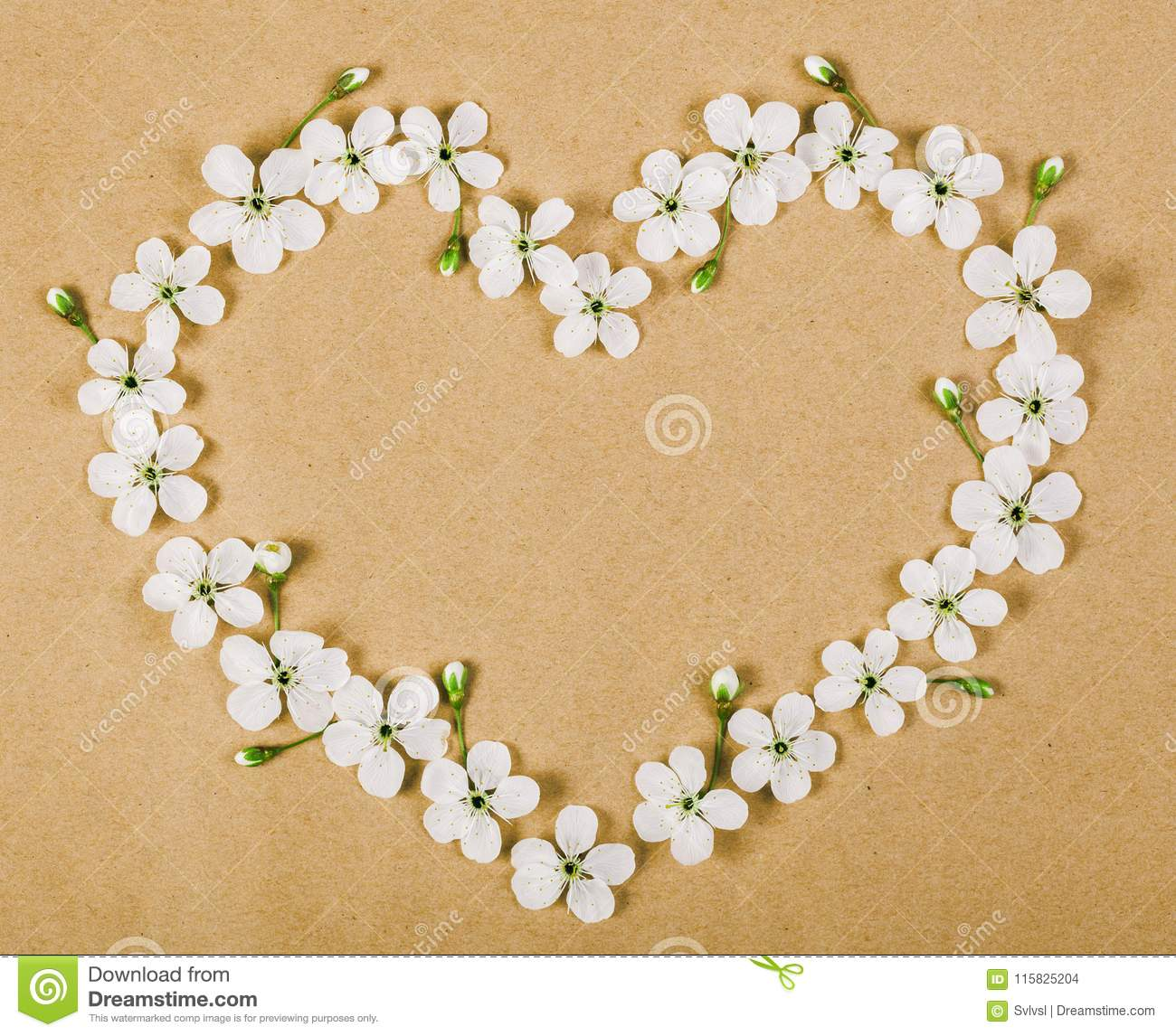 Heart Symbol Made Of White Spring Flowers And Buds On Brown Paper