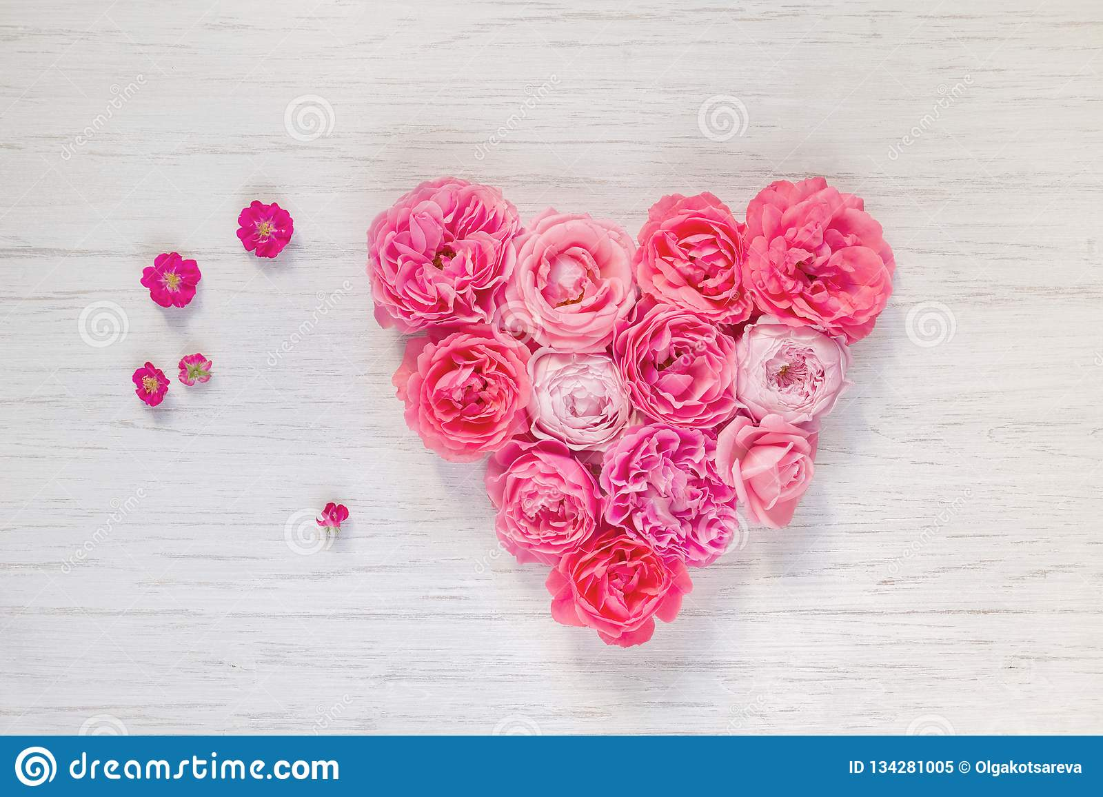 Heart of vintage pink rose flowers on white wooden background, top view