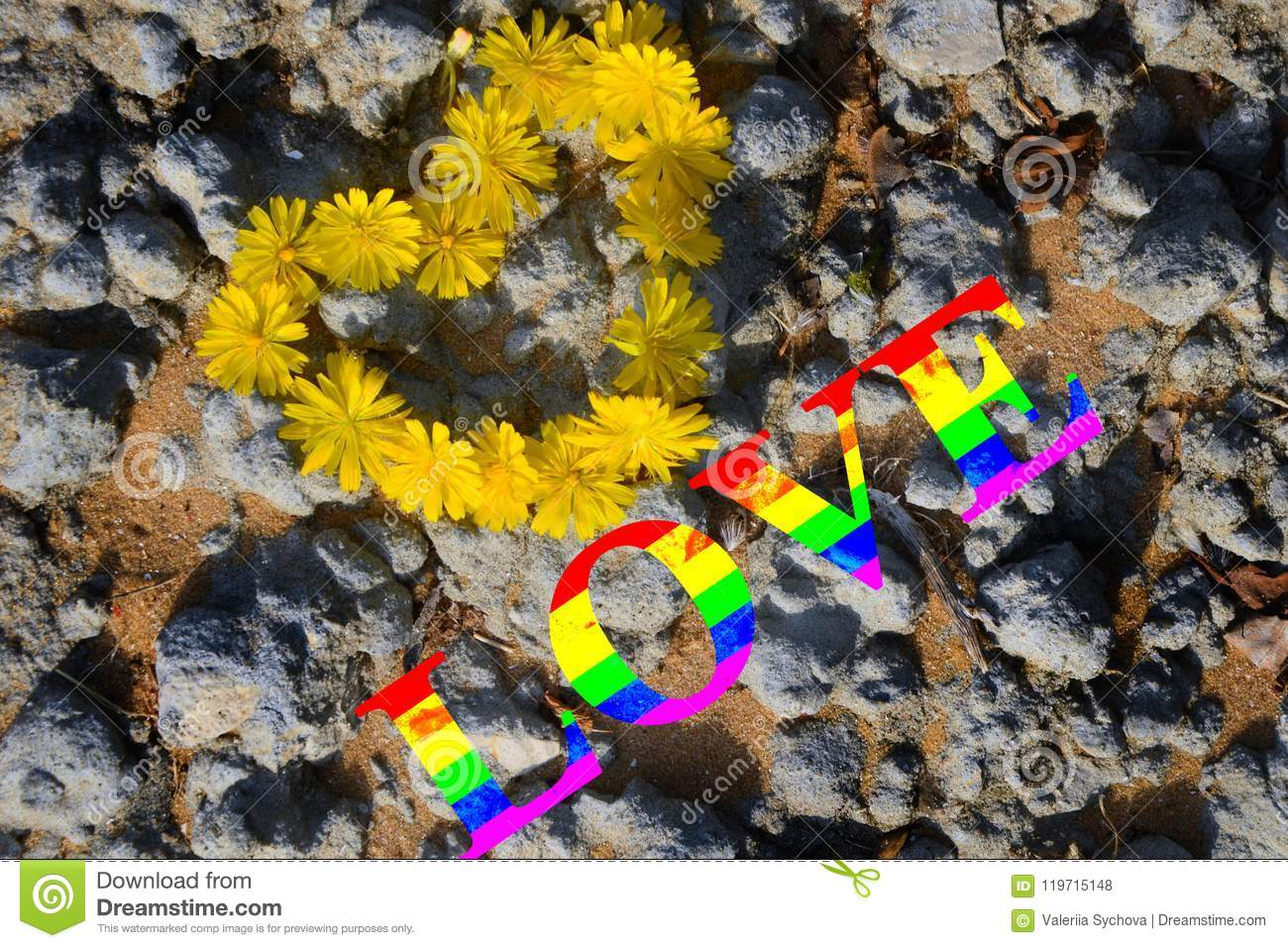 Heart of yellow flowers against the background of sand and gray stones. Multi-colored inscription, rainbow love. the concept of LG