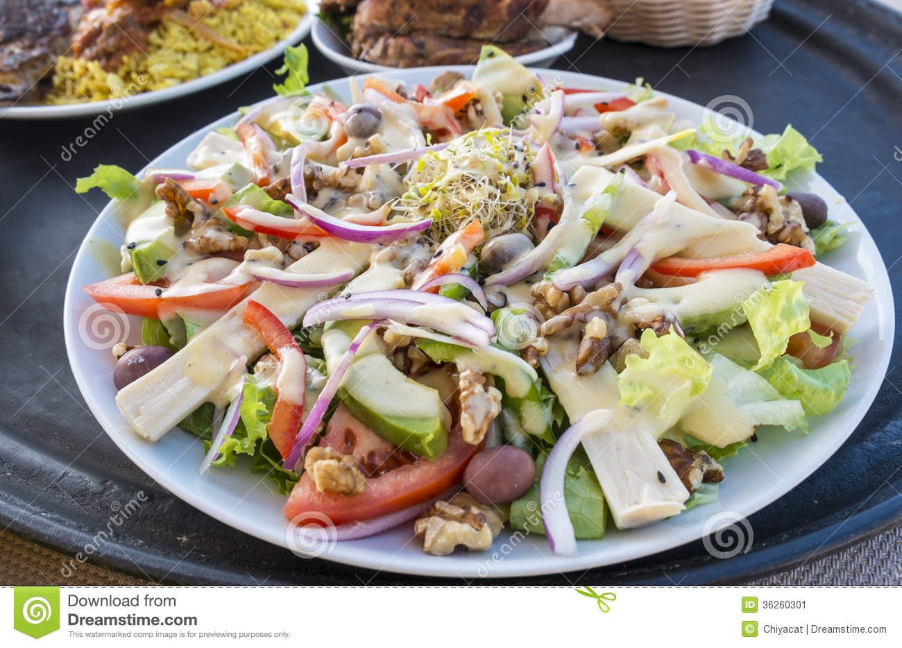 of salad with hearts of palm, avocado, walnuts, olives, red onions ...