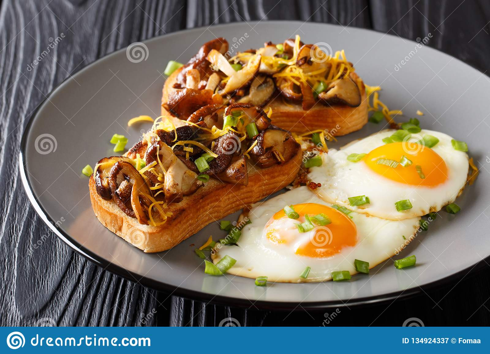 Hearty breakfast of fried toast with shiitake mushrooms and cheddar cheese served with eggs close-up on a plate. horizontal