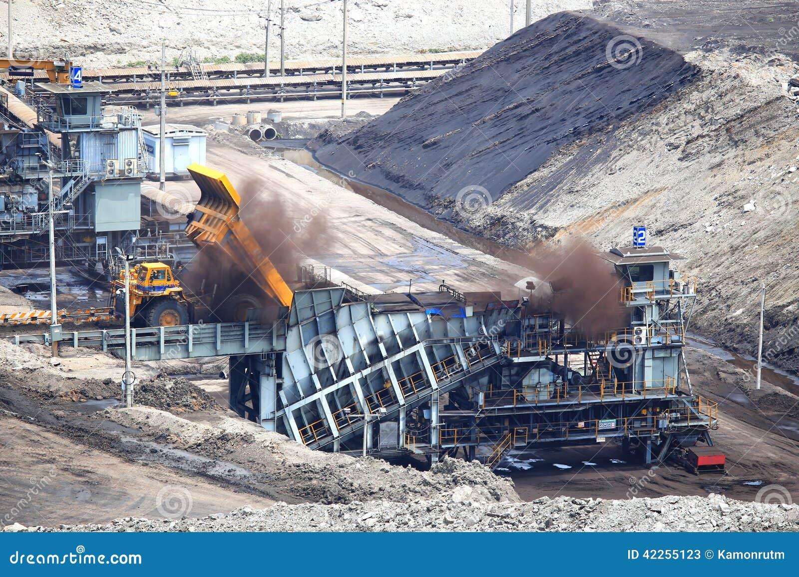 Heavy construction tipper trucks dump coal to the conveyor
