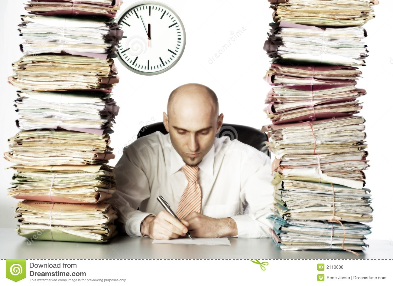 Bald headed businessman surrounded by stacks of files. Concentrating ...