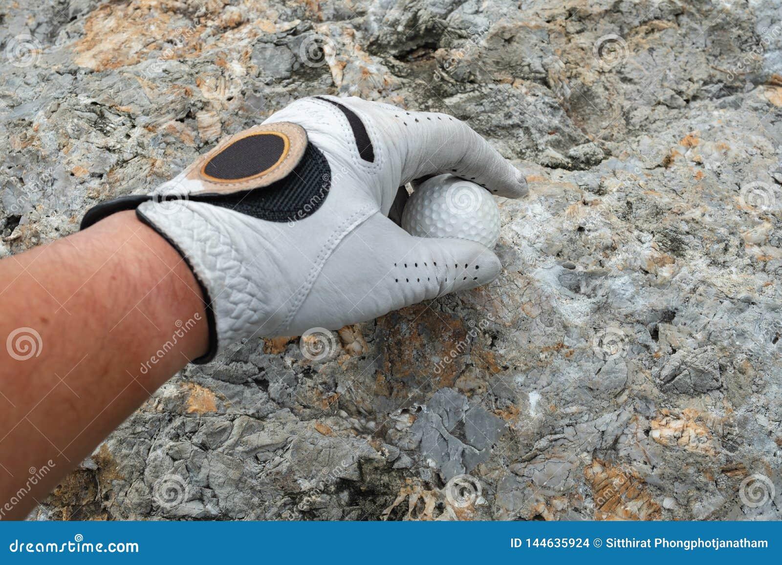 Heben Sie einen Golfball auf Felsen auf