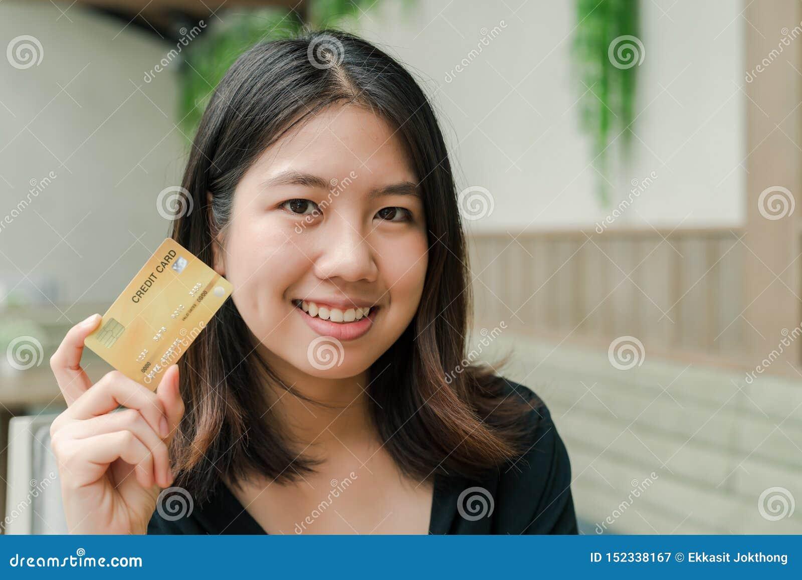 Heeft de close-up Aziatische mooie vrouw die een zwarte overhemdszitting in het huis dragen een creditcard in hand Gelukkig gezic