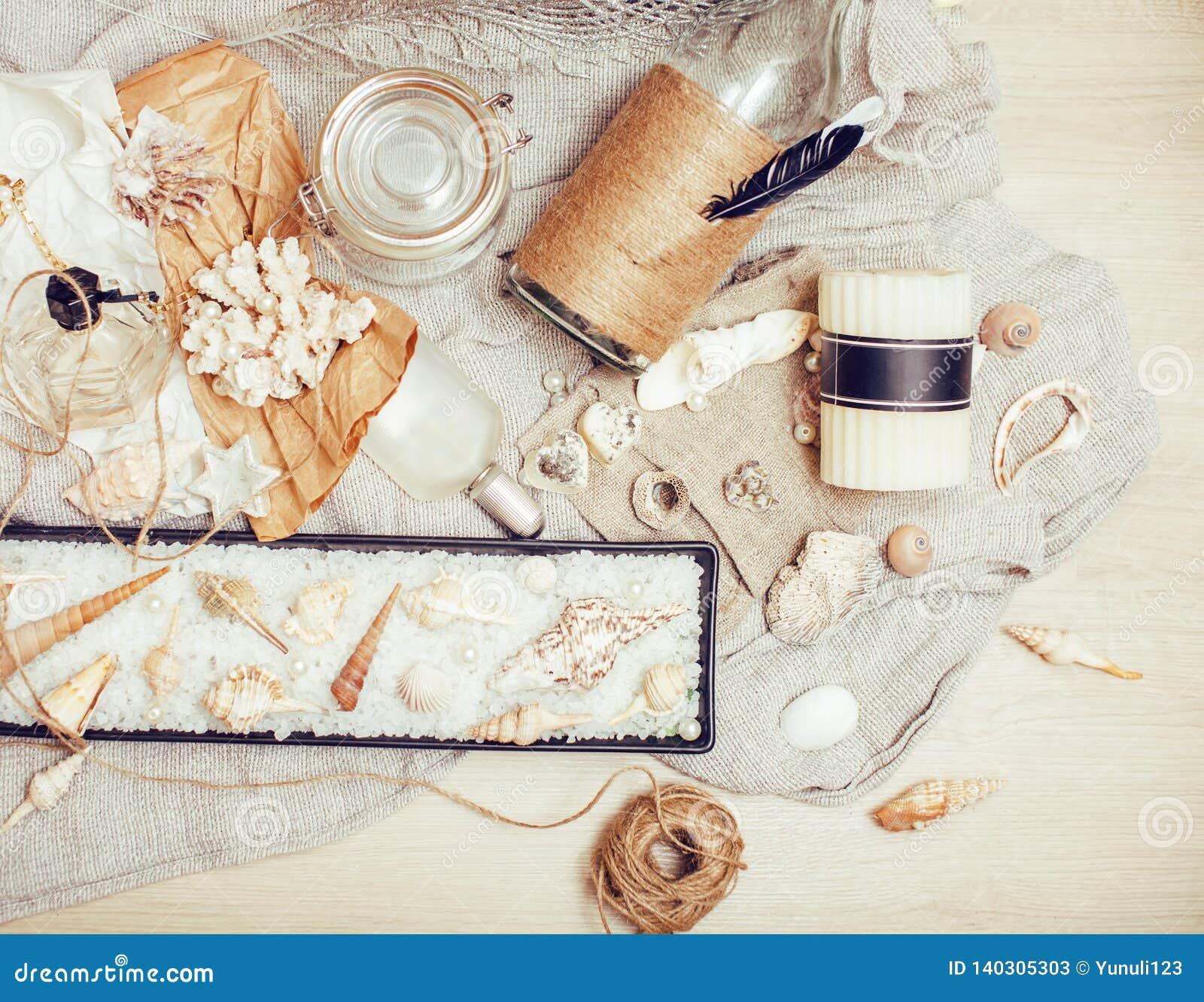 Heel wat overzees thema knoeit binnen als shells, kaarsen, parfum, meisjesmateriaal op linnen, de vrij geweven wijnoogst van de p