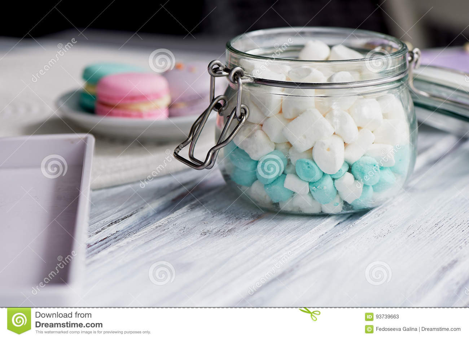 Heemst in witte en blauwe pastelkleurkleuren op een lichte houten oppervlakte In een glaskruik met een scharnierend deksel