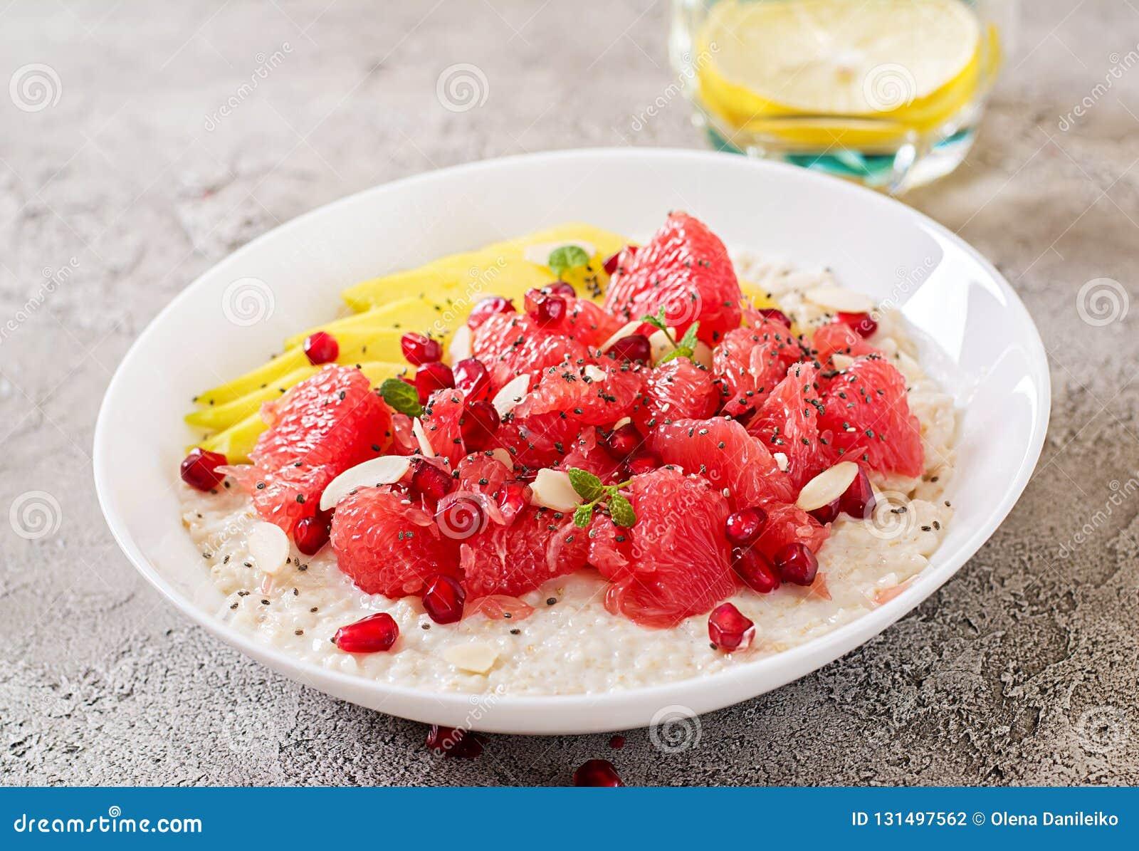 Heerlijk en gezond havermeel met grapefruit, granaatappel, amandel en chiazaden Het gezonde voedsel van de ontbijtgeschiktheid