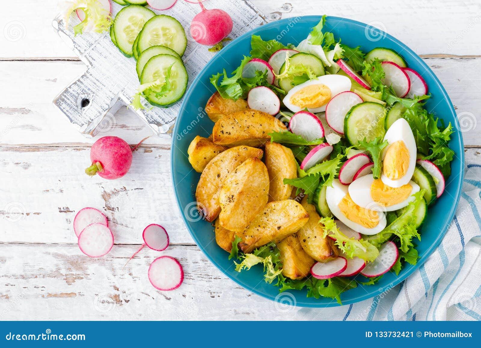 Heerlijke aardappel in de schil, gekookt ei en verse groentesalade van sla, komkommer en radijs De zomermenu voor detoxdieet