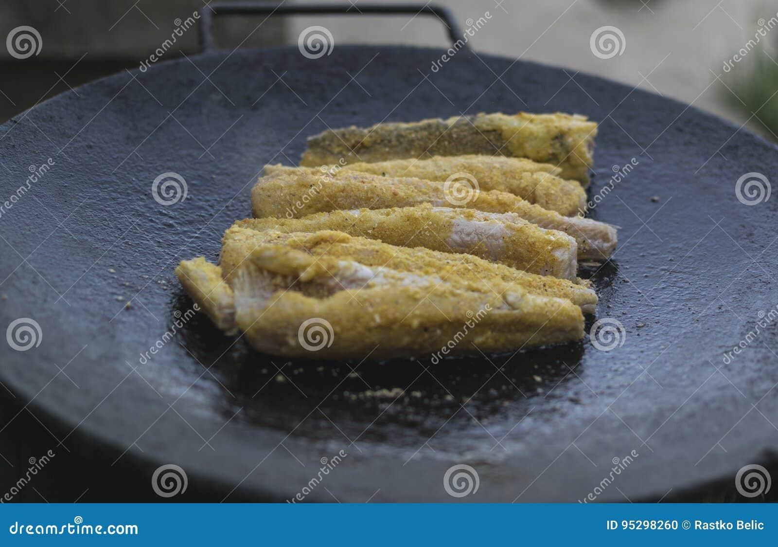 Heerlijke die stokvissenfilets in de pan worden geroosterd