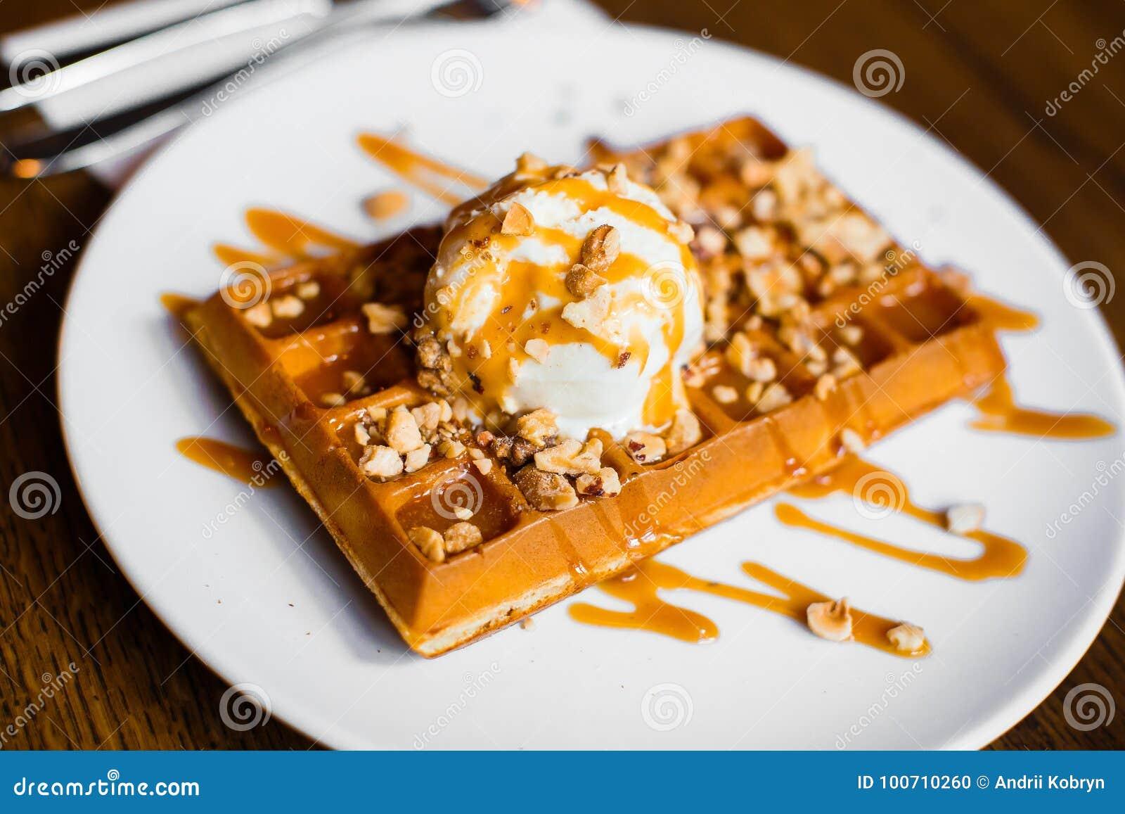 Heerlijke zoete Belgische wafels met smakelijk wit roomijs met karamel en noten Zijclose-upmening