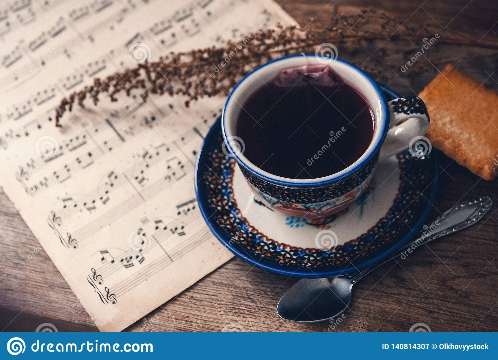 Heet drank en koekje met muzieknoten en de herfstbladeren op een houten lijstoppervlakte Hoogste mening