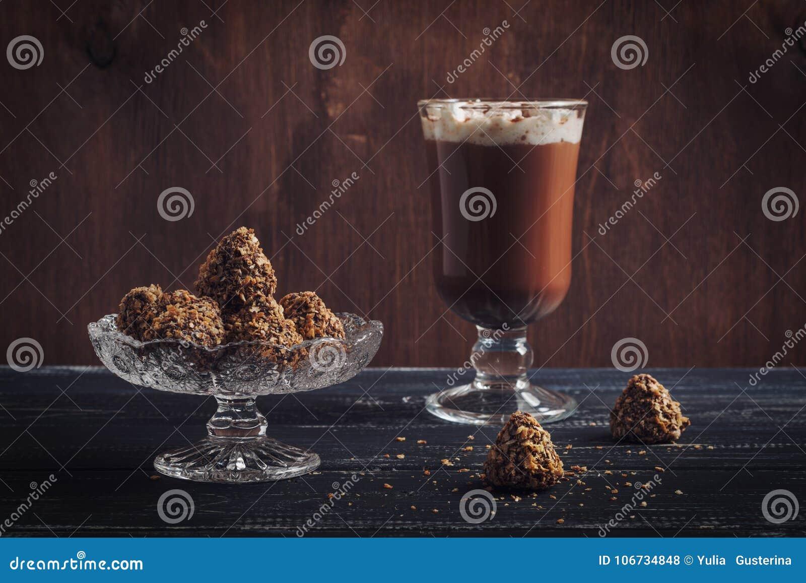 Heiße Schokolade und Bonbons von Trüffeln mit Waffel zerkrümelt auf einem Holztisch Selektiver Fokus