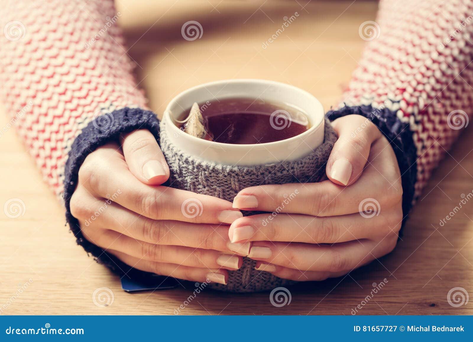 Heißer Becher ` s frau des Tees Erwärmungshände im Retro- Pullover
