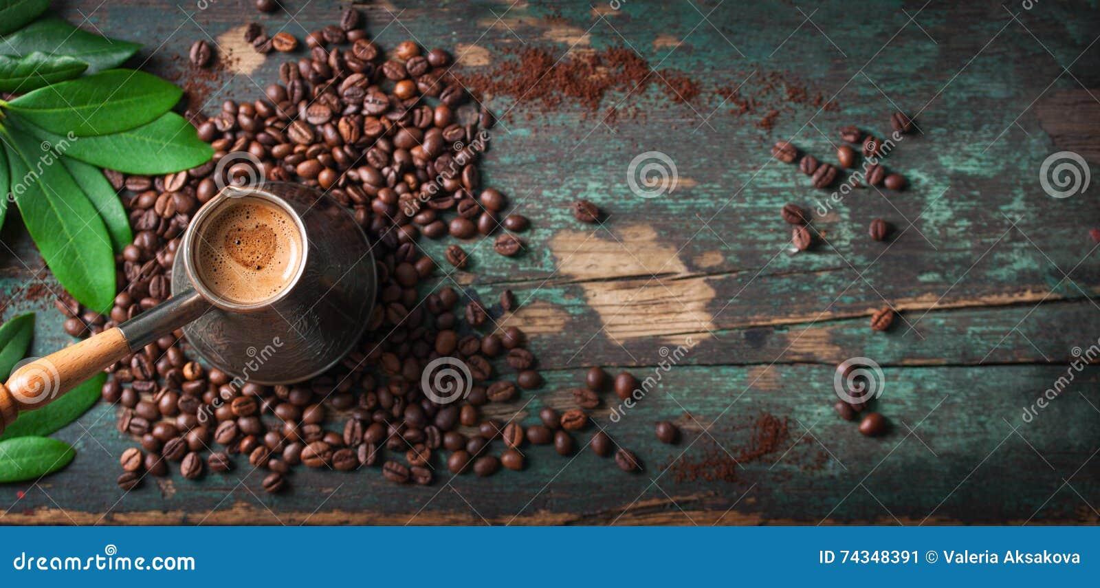 Heißer Kaffee in einer Kaffeekanne oder in einem Türken auf einem hölzernen Hintergrund mit den Kaffeeblättern und -bohnen, horiz