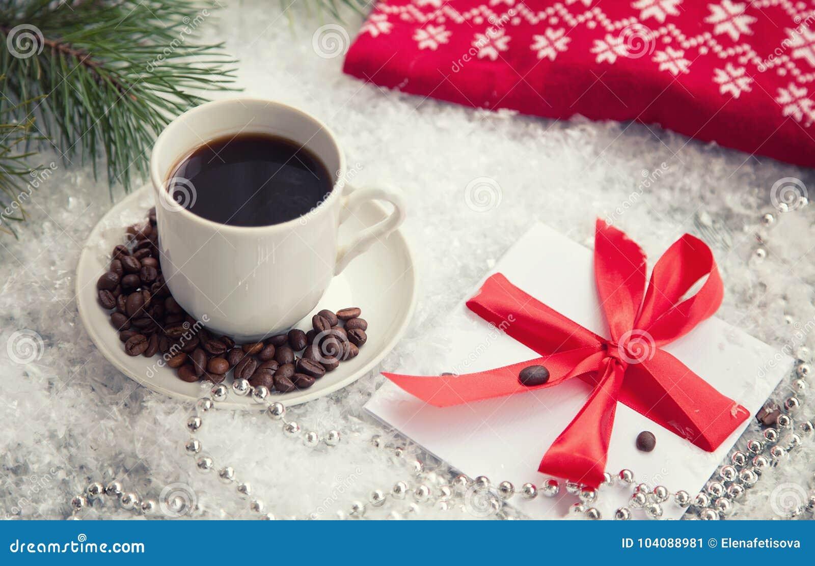 Heißer Kaffee, roter warmer Pullover und Buchstabe von Santa Claus auf einem schneebedeckten Hintergrund