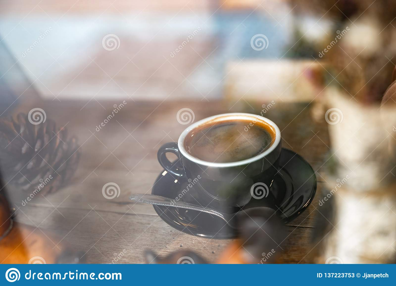 Heißer schwarzer Kaffee in der schwarzen Schale auf Holztisch, durch Fensteransicht