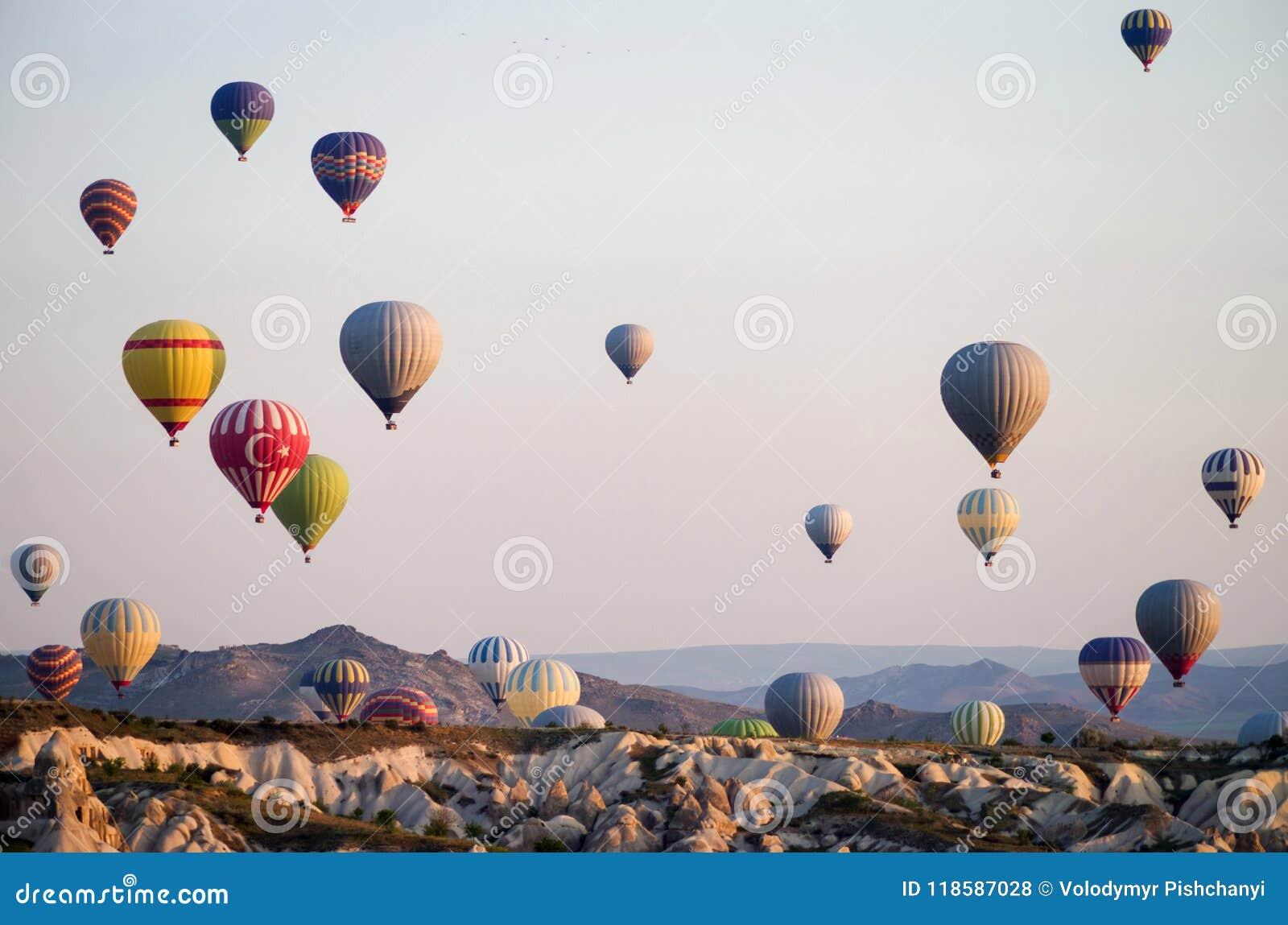Heißluft steigt bei dem Sonnenaufgang im Ballon auf, der über Cappadocia, die Türkei fliegt Ein Ballon mit einer Flagge von der T