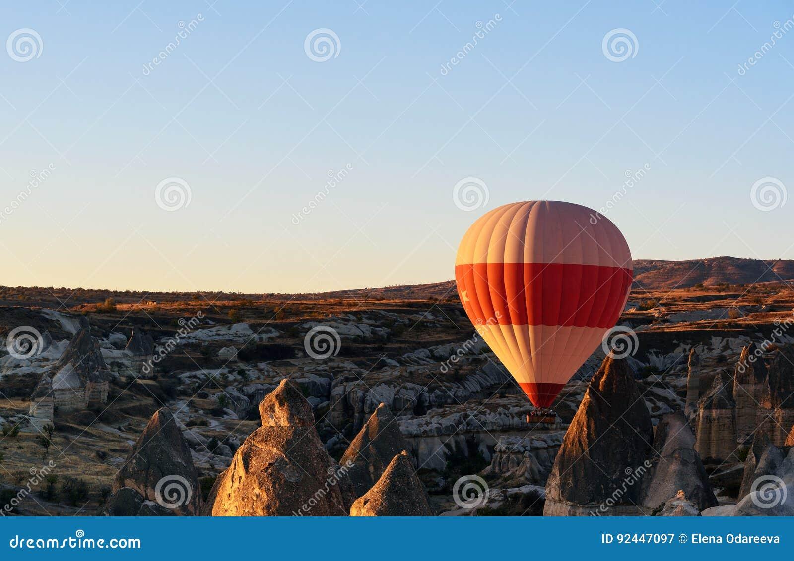 Heißluftballon, der über Tal bei Sonnenaufgang fliegt Cappadocia Die Türkei