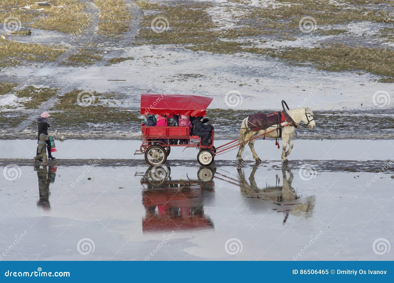 Heilige Petersburg, Rusland - Januari 30 2016: In de Januari-dooi berijden de kleine kinderen een paard op het oude vervoer