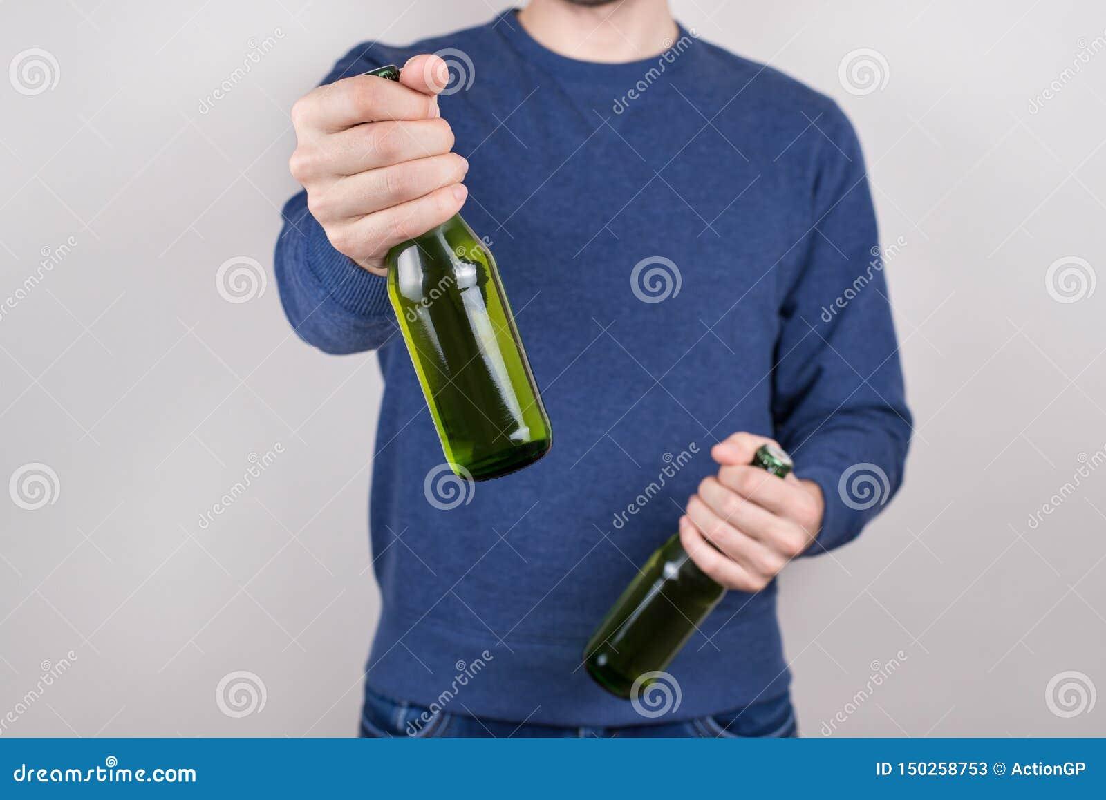 Heiliger Patrick-Tageskonzept Geerntetes Nahaufnahmefoto der betrunkenen hübschen positiven Kerlholdingflasche geschmackvollen fr