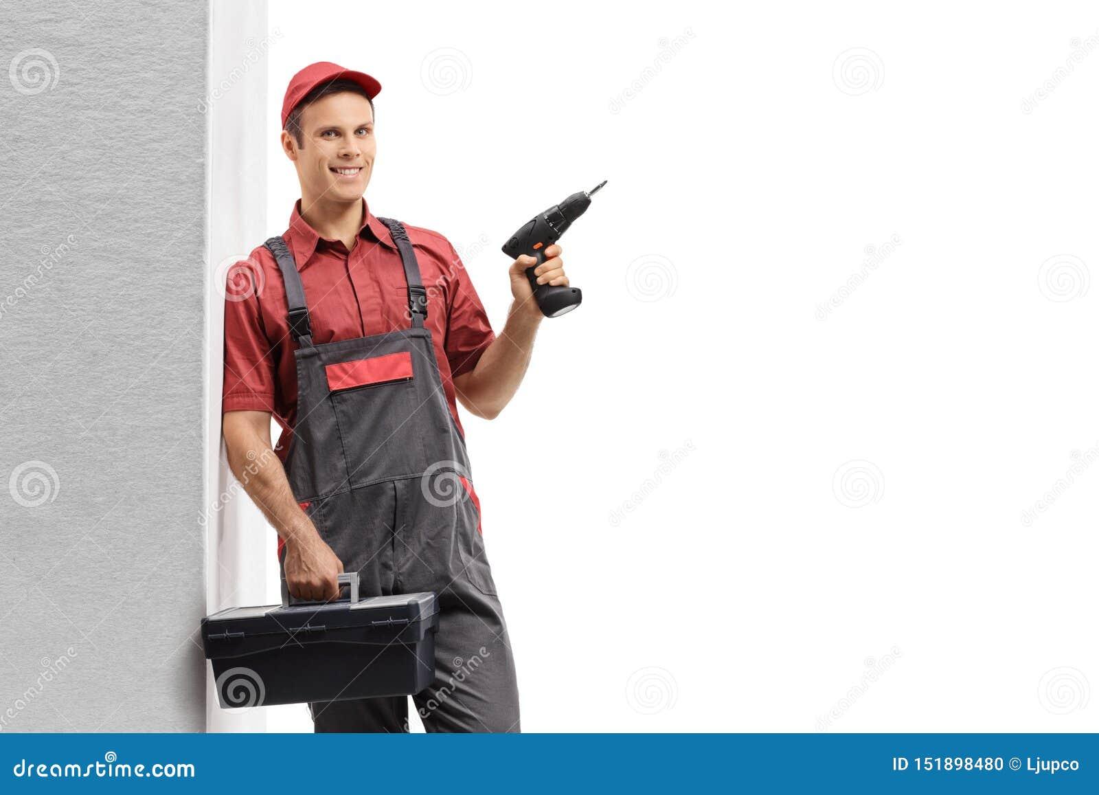Heimwerker, der eine Bohrgerätmaschine und einen Werkzeugkasten lehnend an der Wand und an der Aufstellung hält
