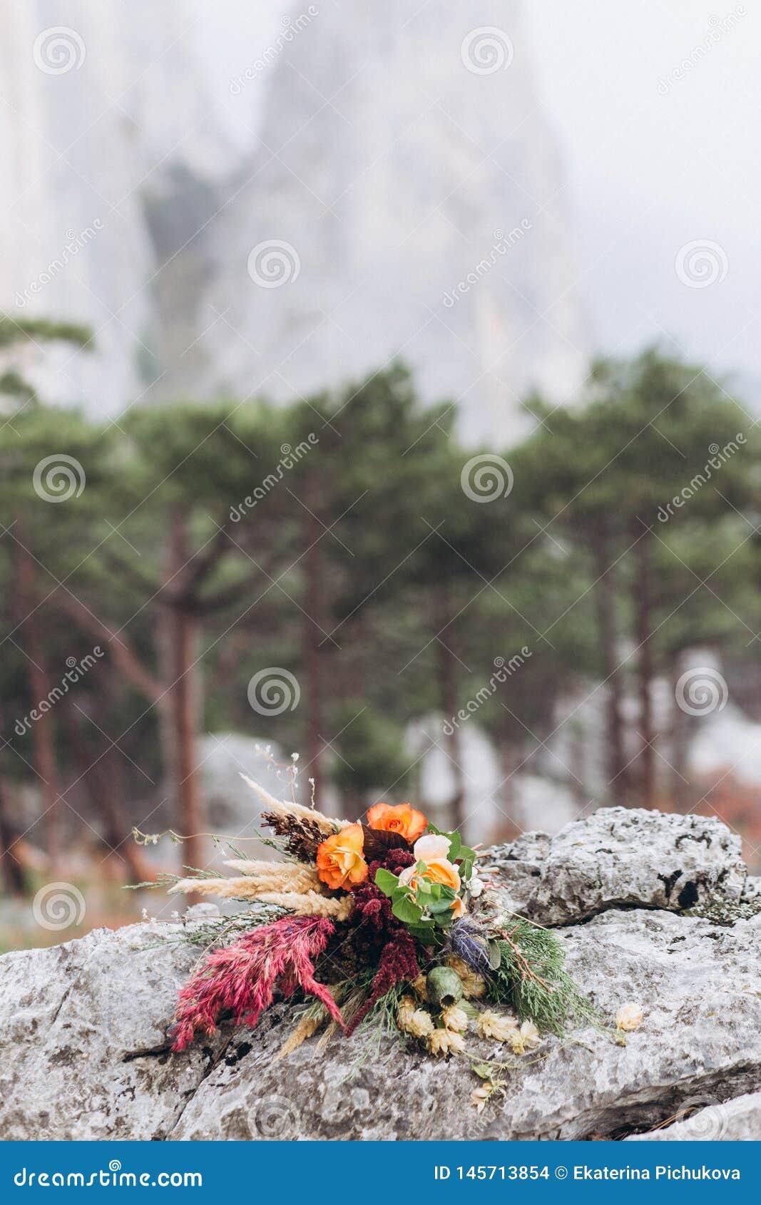 Heiratsassemetrichny-Blumenstrauß auf dem Hintergrund von Herbstbergen und -wäldern