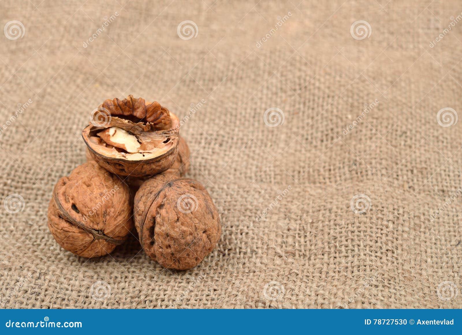 Hela och brutna valnötter på jutebakgrund sund mat selec