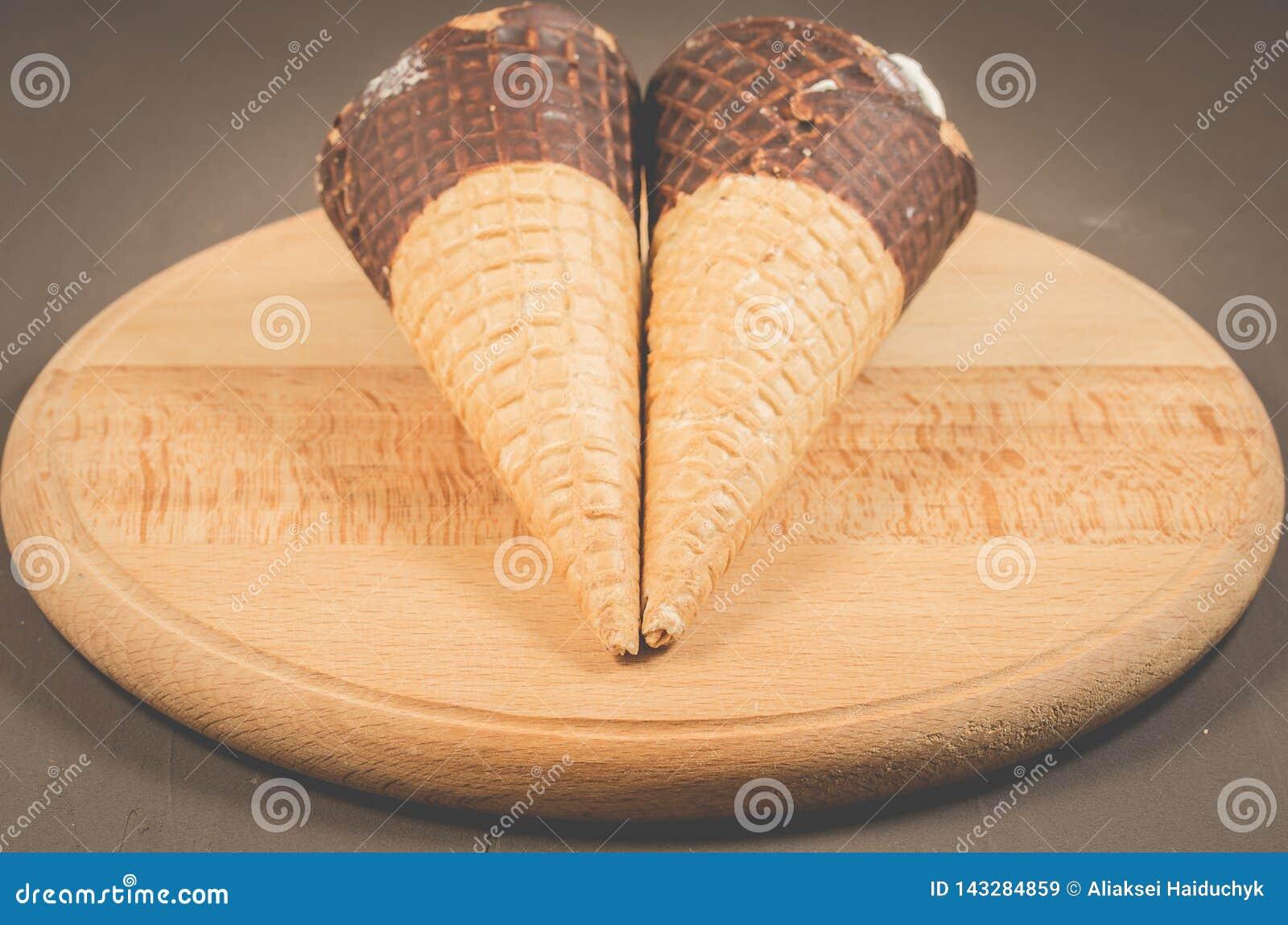 Helado dos con el cono en chocolate en un helado ayuda de madera/dos redondo con el cono en chocolate en una ayuda de madera redo