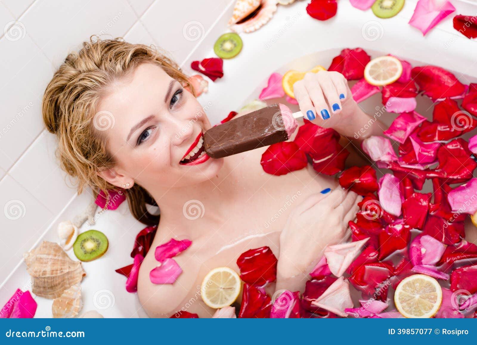 Helado en balneario: la mujer de tentación joven hermosa que come el helado en baño con los pétalos color de rosa y la fruta cort