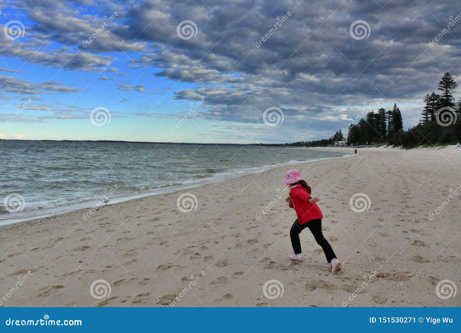 Helder het meisje van Le Sands Beach-The in rood op liep aan het overzees