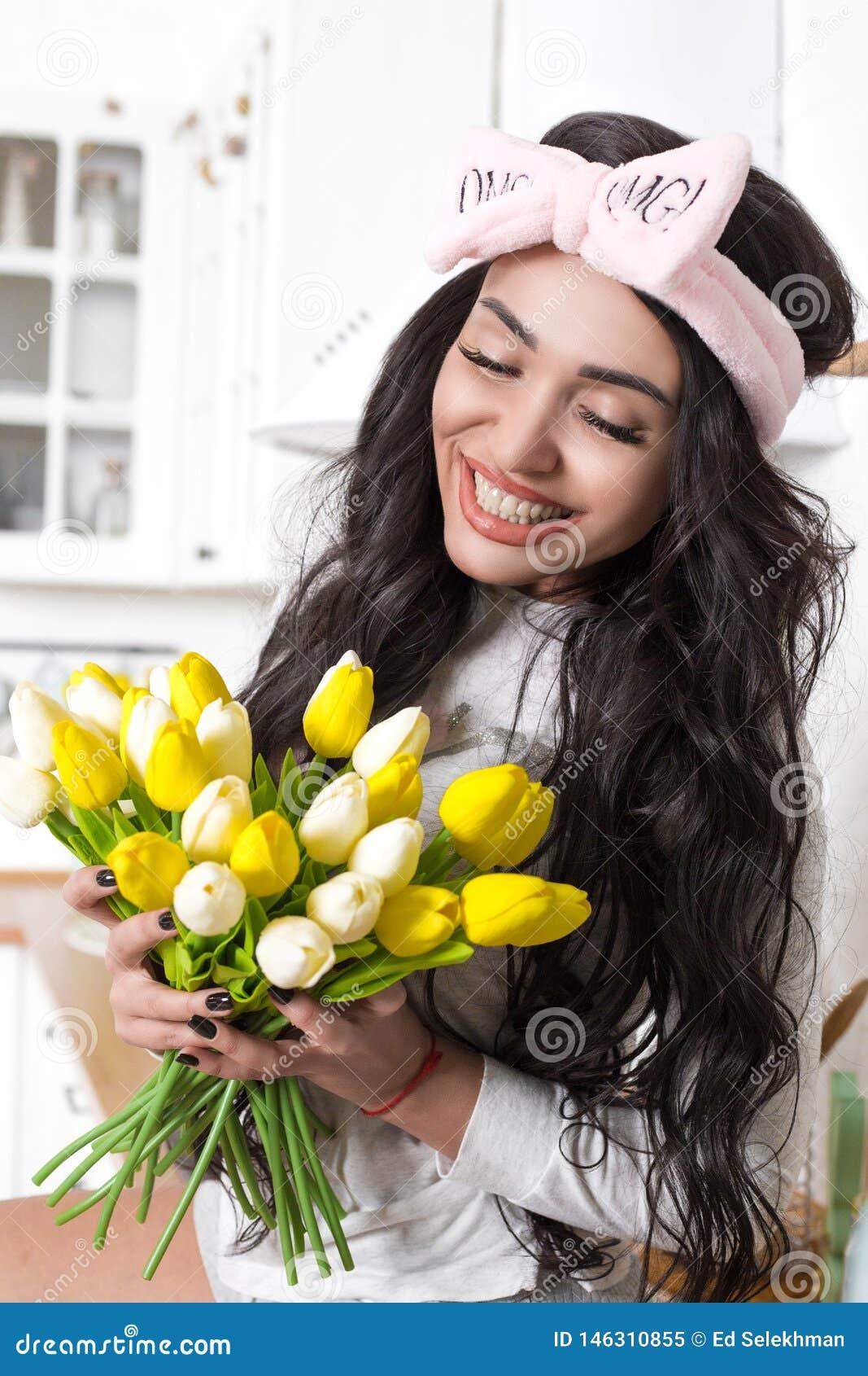 Helder meisje met een glimlach in de keuken met gele tulpen а in de keuken