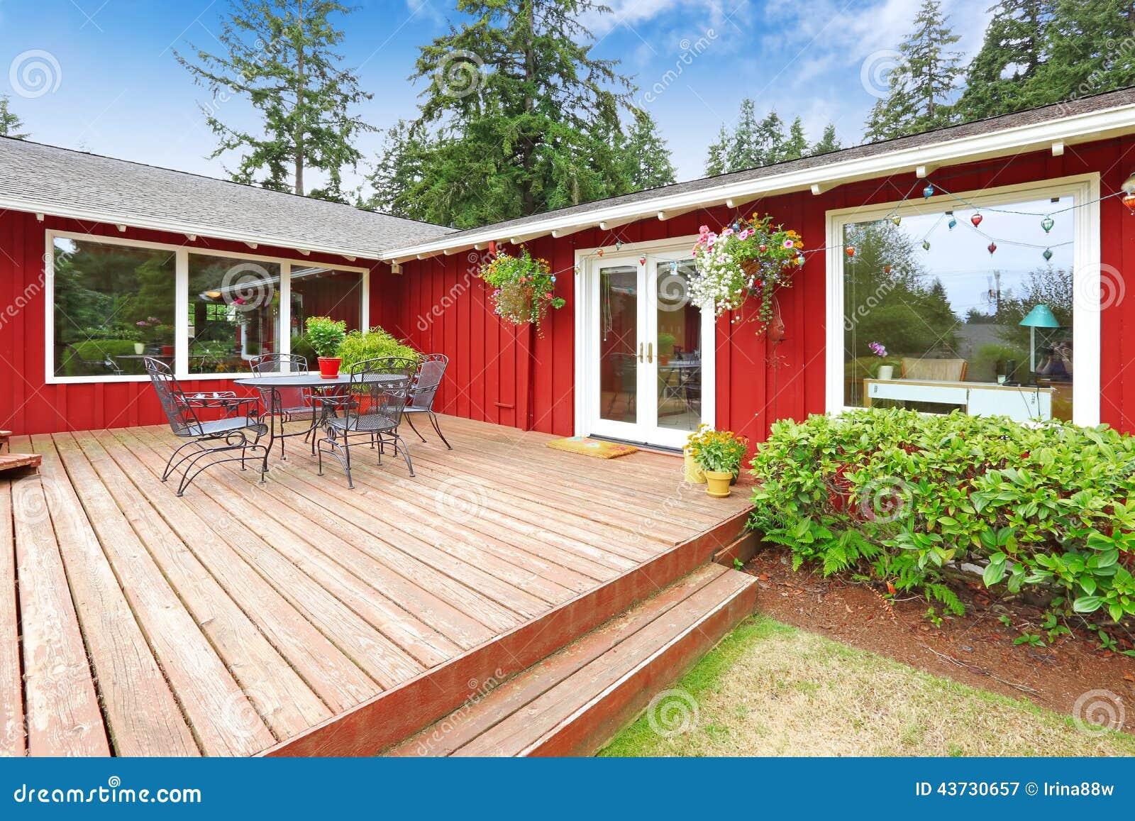 Helder rood huis met van het stakingsdek en terras gebied stock