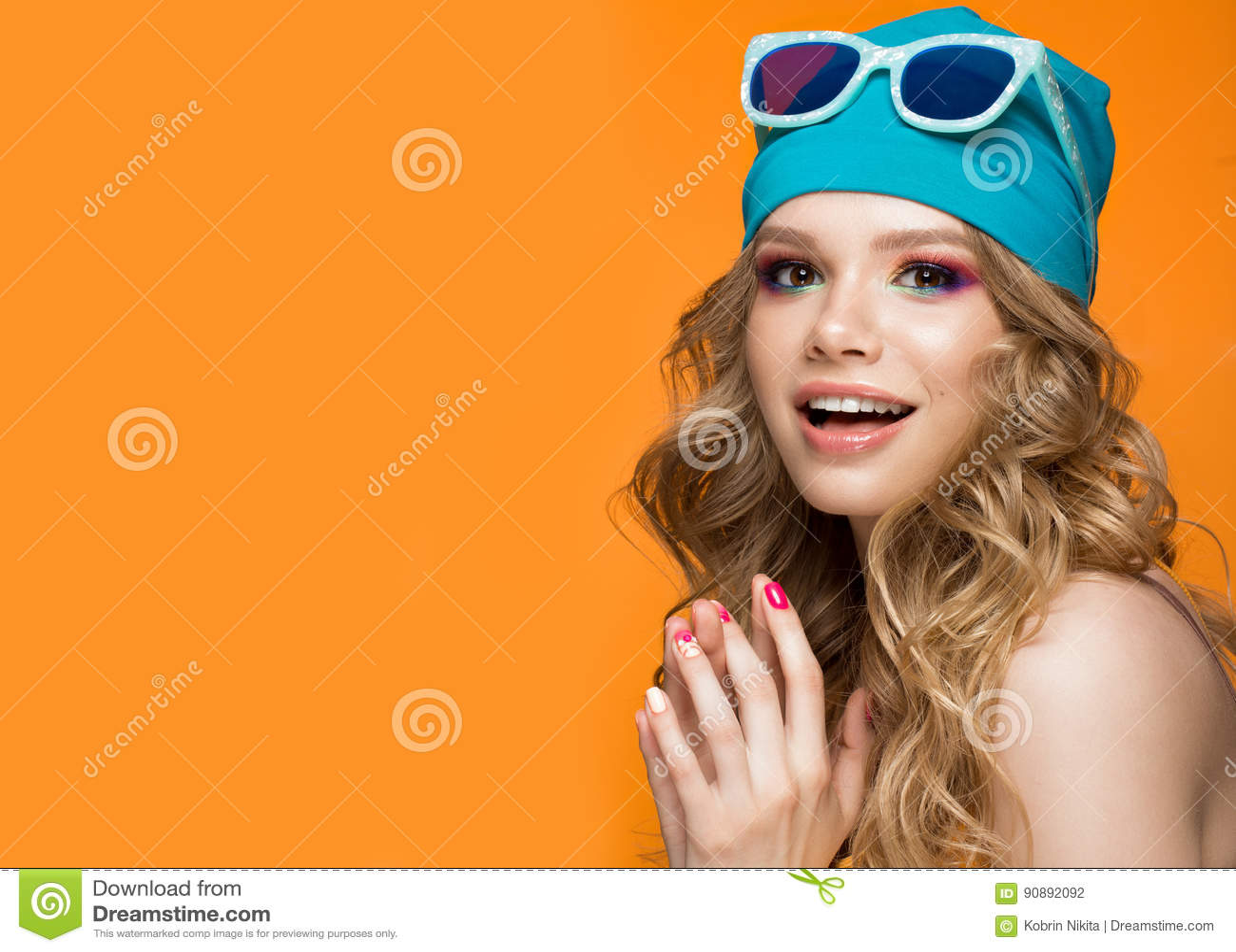 Helder vrolijk meisje in sportenhoed, kleurrijke samenstelling, krullen en roze manicure Het Gezicht van de schoonheid